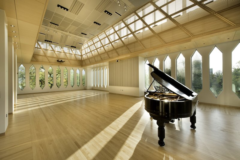 Grand Piano in a large room with windows