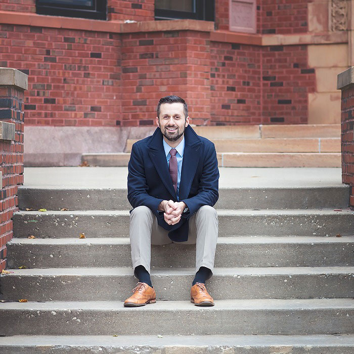 Justin John Moniz sits on steps in front of a brick building